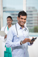 stock-photo-35660288-portrait-of-a-male-indian-doctor-using-a-smart-phone
